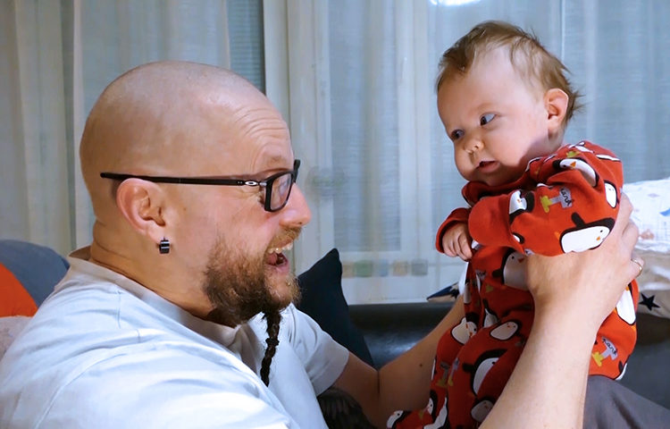Isä nostaa vauvaa ja ilmeilee