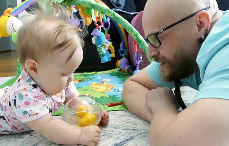 Isä ja vauva leikkivät ankkapallolla