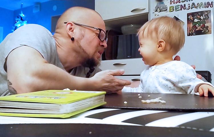 Isä ja lapsi ilmeilevät pöydän ääressä