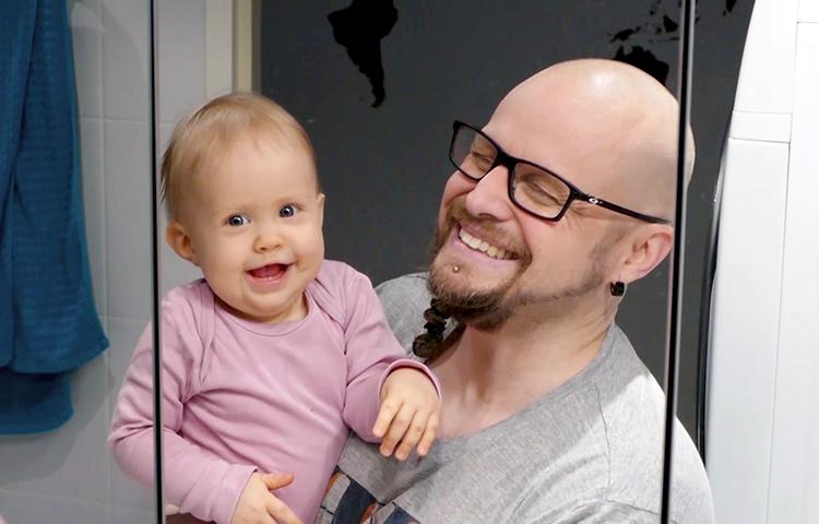 Isä ja vauva hymyilevät peilikuvalle