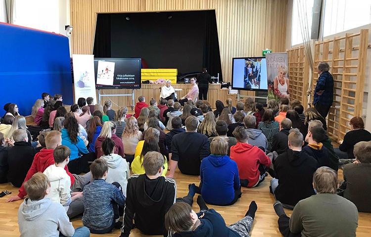 Oppilaat istuvat salin laattialla kuuntelemassa